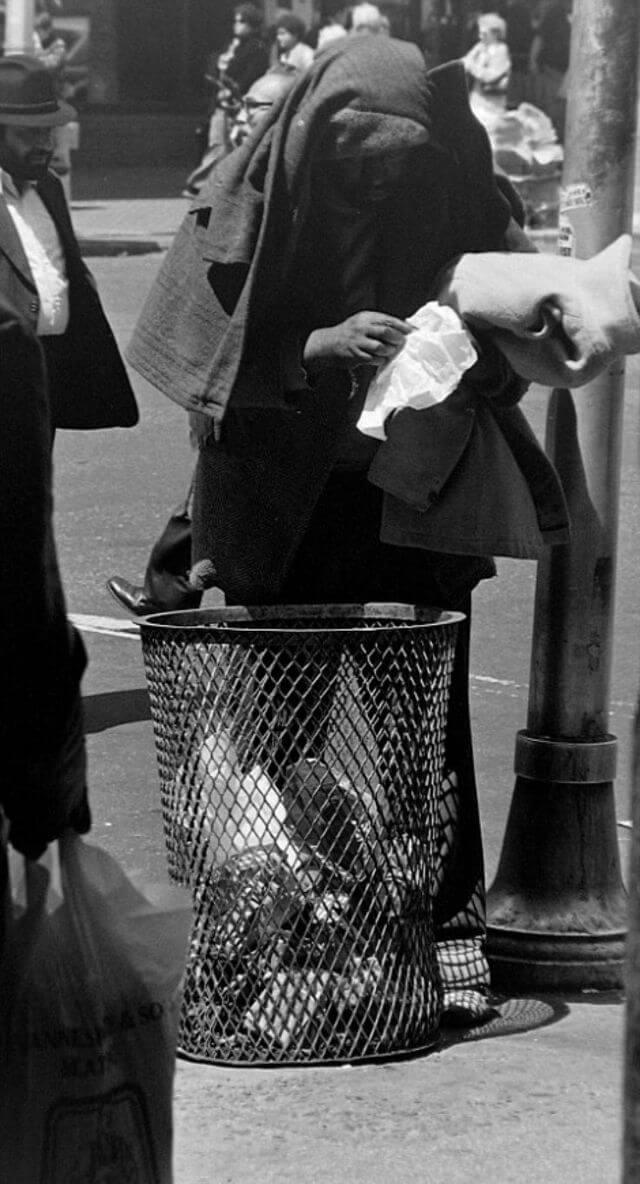 Бездомный роется в мусорном баке